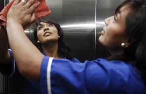 Trabajadora del hogar limpia con trapo una superficie grande de acero inoxidable.