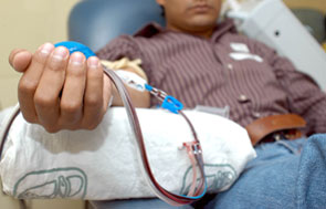 Una persona sentada, con el brazo extendido, dona sangre.