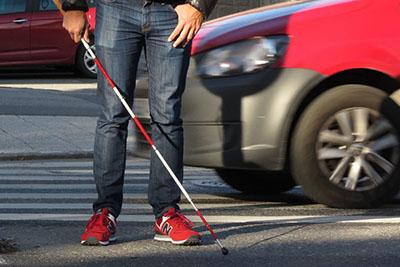 Foto de una persona ciega usando el bastón en la calle