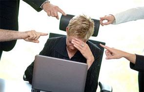 Mujer con laptop es señalada por varias manos en una representación de mobbying o acoso laboral.