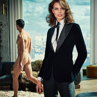 Se muestra a una mujer vestida con un traje y a un hombre desnudo caminando al lado de ella