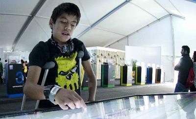 Imagen que muestra a niño en muletas interactuando con una pantalla digital