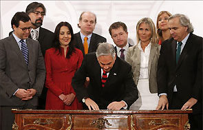 El presidente de Chile, Sebasti�n Pi�era, firma la ley, al centro de la foto, inclinado sobre un escritorio y rodeado de testigos.