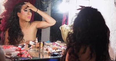 Persona trans viendose al espejo y maquillándose