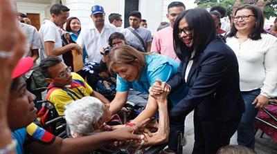 Integrantes de la asamblea nacional  constituyente de Venezuela saludan a personas con discapacidad en un acto de celebración