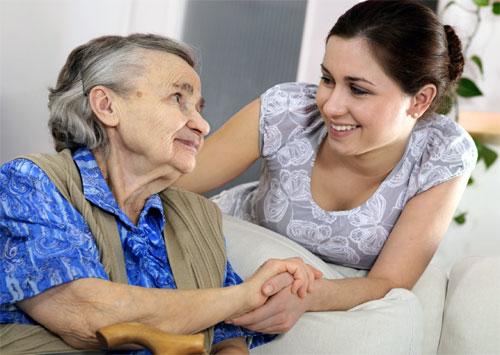 Mujer adulta mayor toma de la mano a una mujer más joven.
