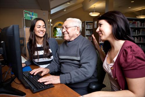 Adulto mayor trabaja en computadora asesorados por dos mujeres jóvenes.