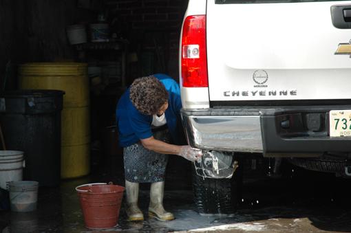 Trabajadora del hogar lava camioneta todo terreno del empleador.
