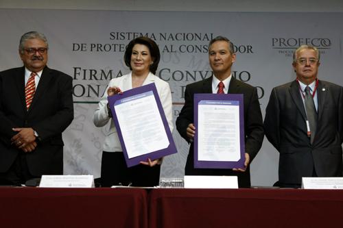 Los titulares de las instituciones muestran el convenio ya firmado.