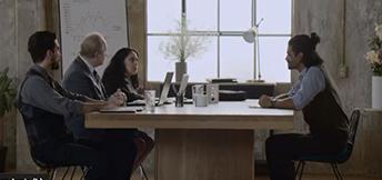 Imagen que muestra a un joven sentado con otras personas en un escritorio